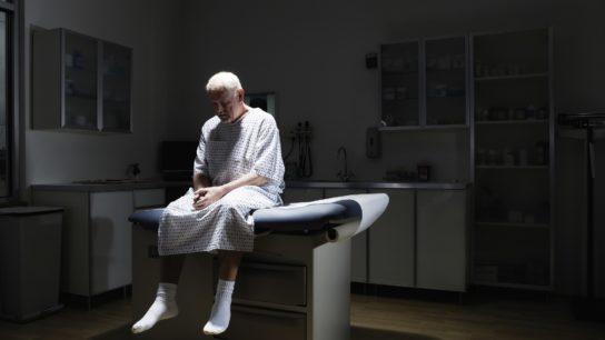 Depressed man sitting on examination table